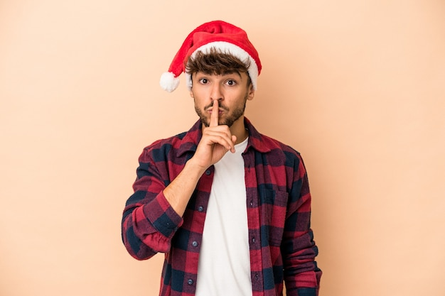 Young arab man celebrating christmas isolated on beige background keeping a secret or asking for silence.