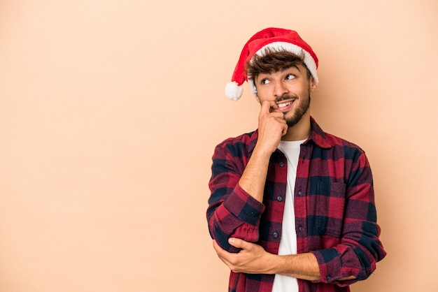 Young arab man celebrating christmas isolated on beige background relaxed thinking about something looking at a copy space.