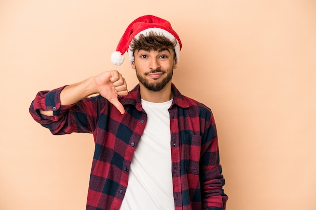 Young arab man celebrating christmas isolated on beige background showing a dislike gesture, thumbs down. disagreement concept.