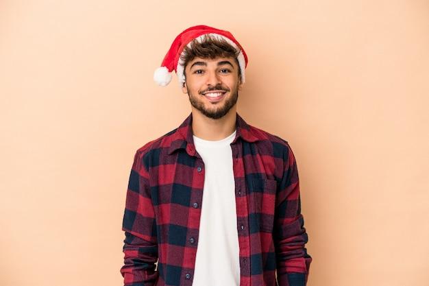 クリスマスを祝う若いアラブ人は、幸せ、笑顔、陽気なベージュの背景に分離されました。