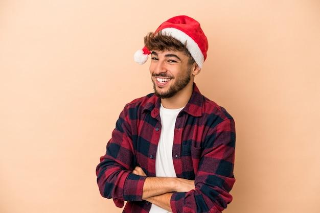 笑って楽しんでいるベージュの背景に分離されたクリスマスを祝う若いアラブ人。