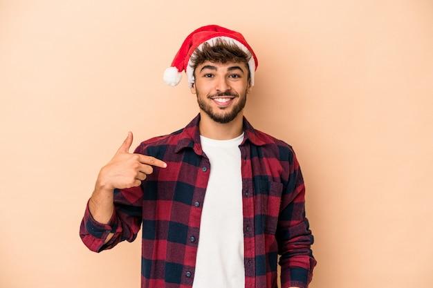 誇りと自信を持って、シャツのコピースペースを手で指しているベージュの背景の人に分離されたクリスマスを祝う若いアラブ人