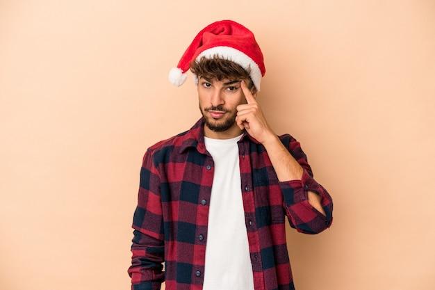 クリスマスを祝う若いアラブ人は、ベージュの背景に指で寺院を指して、考えて、タスクに焦点を当てた。