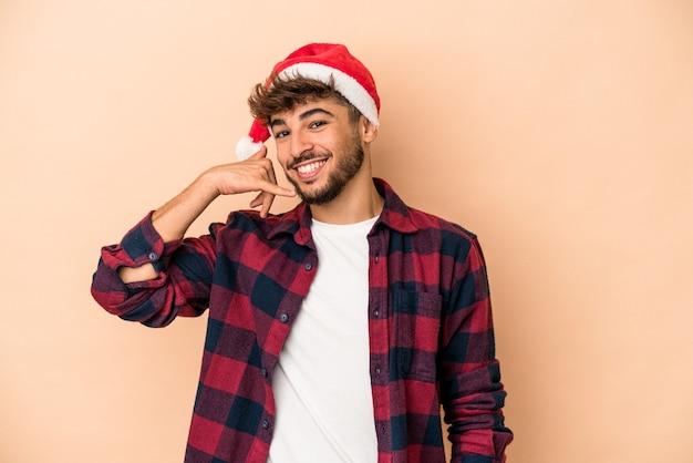 指で携帯電話の呼び出しジェスチャーを示すベージュの背景に分離されたクリスマスを祝う若いアラブ人。