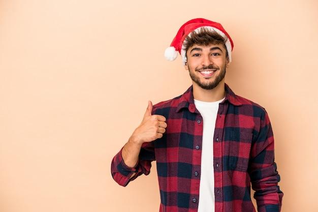 笑顔と親指を上げるベージュの背景に分離されたクリスマスを祝う若いアラブ人
