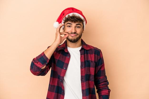秘密を保持している唇に指でベージュの背景に分離されたクリスマスを祝う若いアラブ人。