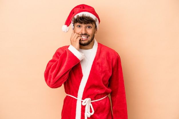 Young arab man disguised as santa claus isolated on beige background biting fingernails, nervous and very anxious.