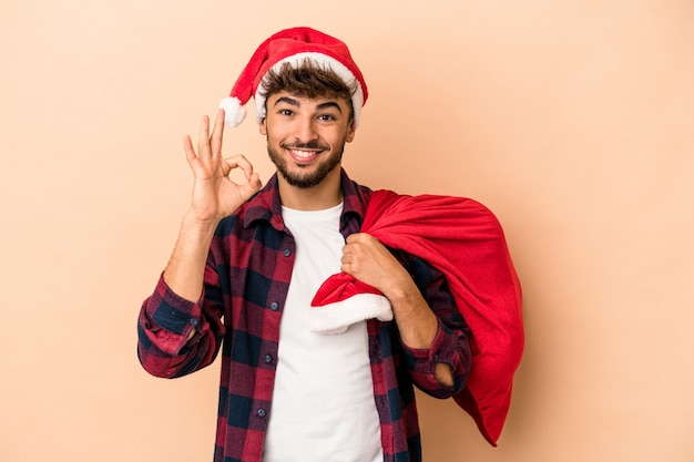 Young arab man disguised as santa claus isolated on beige background cheerful and confident showing ok gesture.