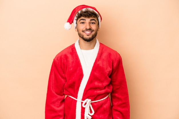 Young arab man disguised as santa claus isolated on beige background happy, smiling and cheerful.