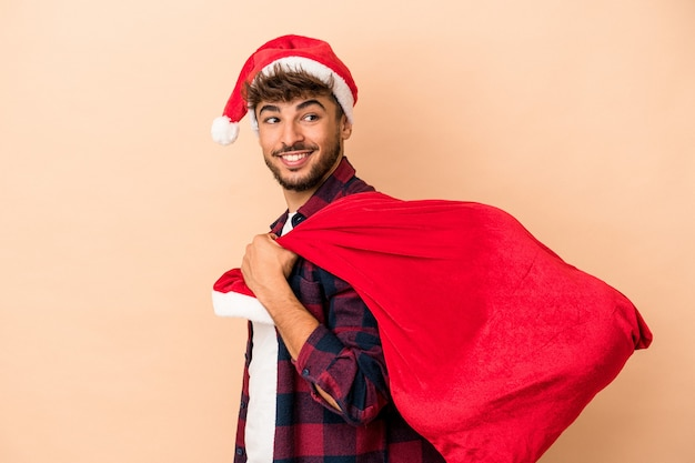 Young arab man disguised as santa claus isolated on beige background looks aside smiling, cheerful and pleasant.