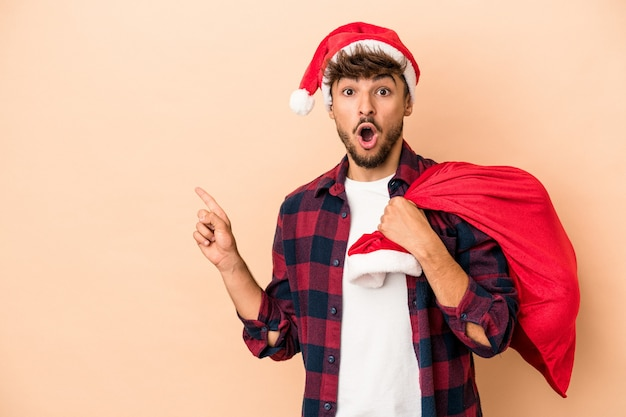 Young arab man disguised as santa claus isolated on beige background pointing to the side
