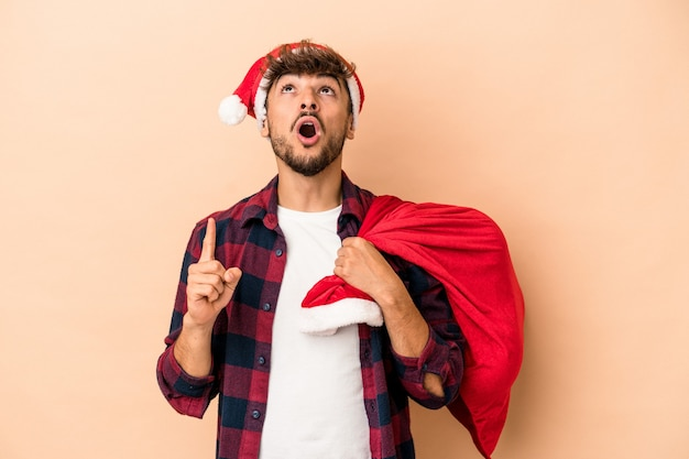 Young arab man disguised as santa claus isolated on beige background pointing upside with opened mouth.