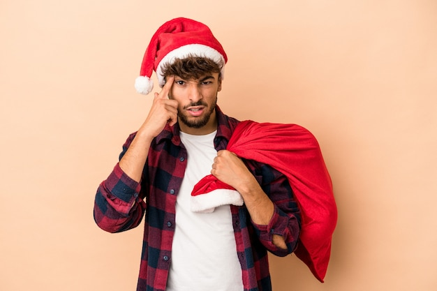 Young arab man disguised as santa claus isolated on beige background showing a disappointment gesture with forefinger.