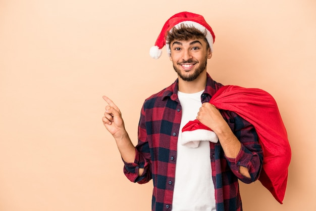 Young arab man disguised as santa claus isolated on beige background smiling and pointing aside, showing something at blank space.