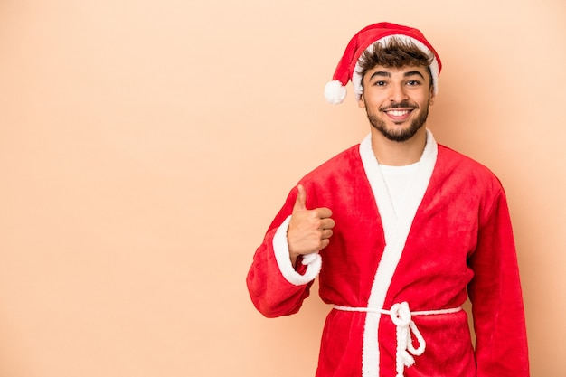 Young arab man disguised as santa claus isolated on beige background smiling and raising thumb up