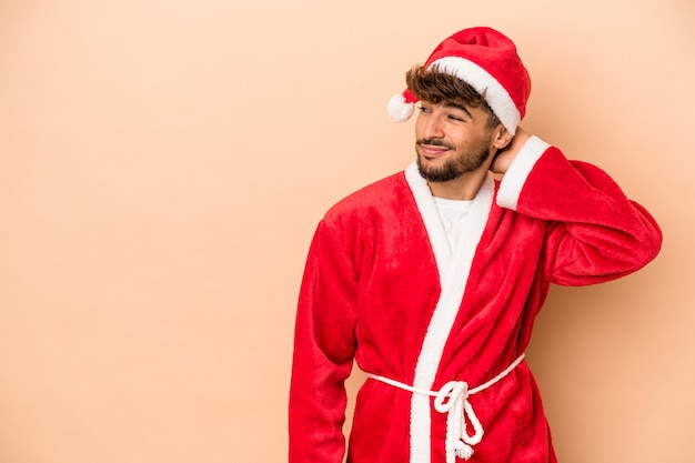Young arab man disguised as santa claus isolated on beige background touching back of head, thinking and making a choice.