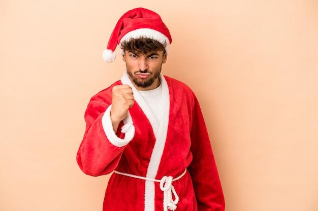 산타클로스로 위장한 젊은 아랍 남자는 베이지색 배경에 고립되어 카메라에 주먹을 대고 공격적인 표정을 짓고 있습니다.