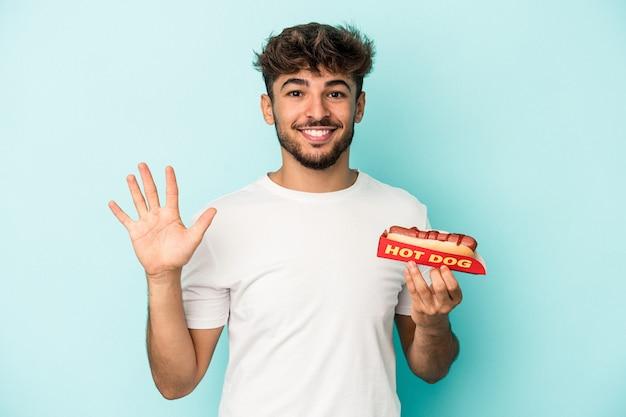 青い背景に分離されたホットドッグを持っている若いアラブ人は、指で5番を示して陽気に笑っています。