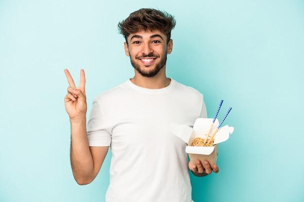 青い背景に分離された持ち帰り用の麺を持っている若いアラブ人は、指で平和のシンボルを喜んで気楽に示しています。