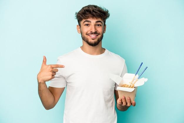 誇りと自信を持って、シャツのコピースペースを手で指している青い背景の人に分離されたテイクアウト麺を保持している若いアラブ人