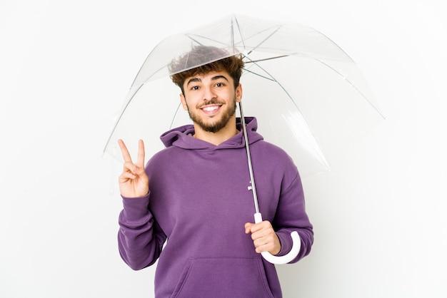 指で平和のシンボルを示す楽しくてのんきな傘を持っている若いアラブ人