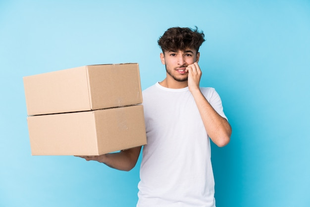 Young arab man holding boxes isolated biting fingernails, nervous and very anxious.