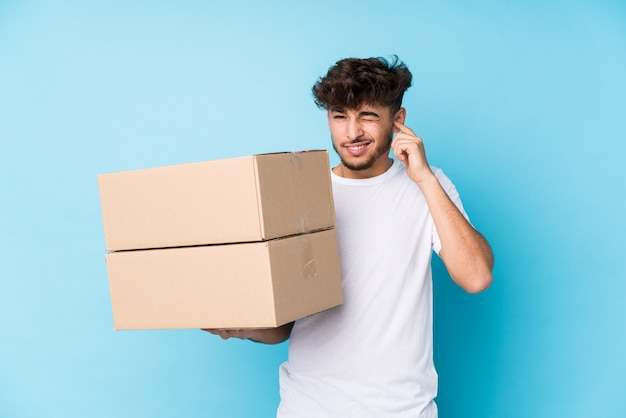 Young arab man holding boxes isolated covering ears with hands.