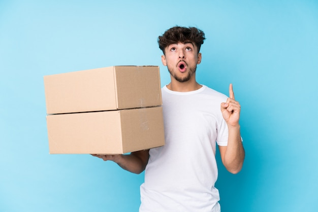Young arab man holding boxes isolated pointing upside with opened mouth.