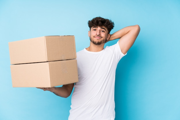 箱を持っている若いアラブ人は、頭の後ろに触れて、考えて、選択をします。