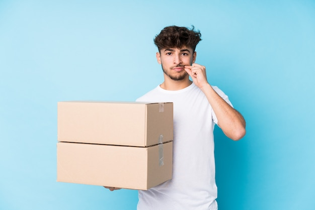 Young arab man holding boxes isolated with fingers on lips keeping a secret