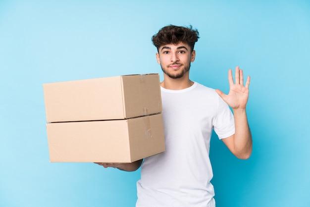 Молодой арабский мужчина держит коробки