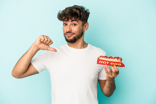 Young arab man holding a hotdog isolated on blue background feels proud and self confident, example to follow.