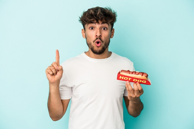 Young arab man holding a hotdog isolated on blue background having some great idea, concept of creativity.