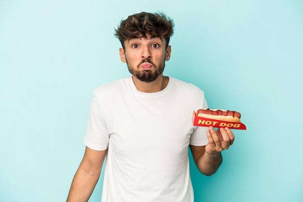 Young arab man holding a hotdog isolated on blue background shrugs shoulders and open eyes confused.