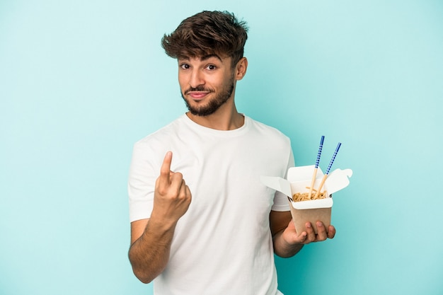 Young arab man holding a take away noodles isolated on blue background pointing with finger at you as if inviting come closer.