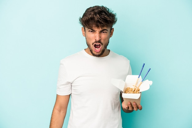 Young arab man holding a take away noodles isolated on blue background screaming very angry and aggressive.