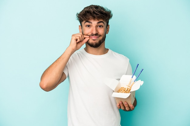 Young arab man holding a take away noodles isolated on blue background with fingers on lips keeping a secret.