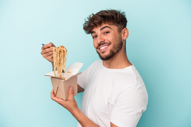 Young arab man holding a take away noodles isolated on blue background
