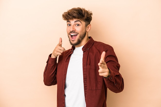 Young arab man isolated on beige background cheerful smiles pointing to front.