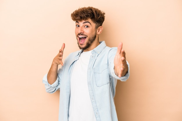 Young arab man isolated on beige background feels confident giving a hug to the camera.