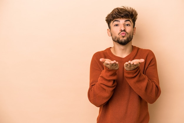 Young arab man isolated on beige background folding lips and holding palms to send air kiss.