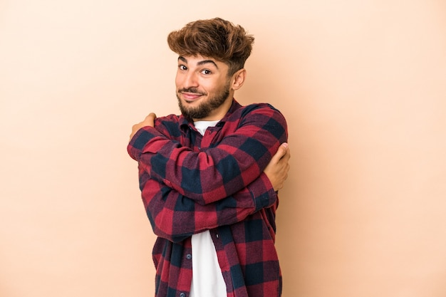 Young arab man isolated on beige background hugs, smiling carefree and happy.