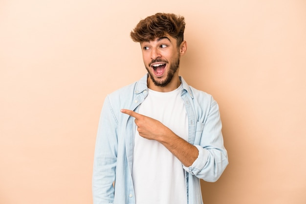 Young arab man isolated on beige background looks aside smiling, cheerful and pleasant.