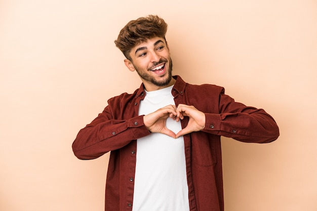Young arab man isolated on beige background smiling and showing a heart shape with hands.