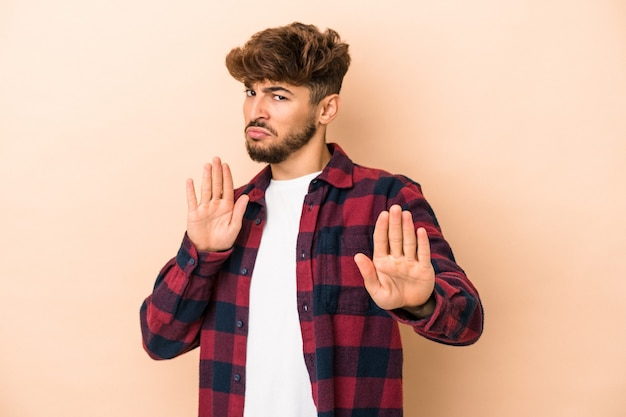 Young arab man isolated on beige background standing with outstretched hand showing stop sign, preventing you.