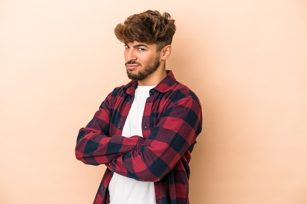 Young arab man isolated on beige background suspicious, uncertain, examining you.