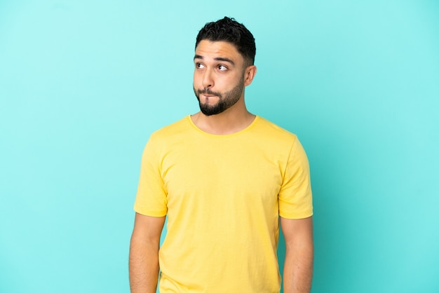 Young arab man isolated on blue background having doubts while looking up
