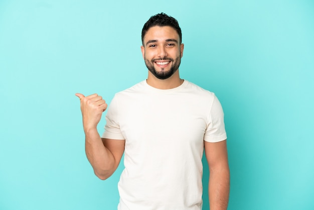 Young arab man isolated on blue background pointing to the side to present a product