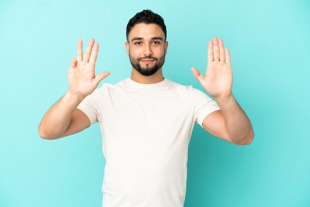 指で9を数える青い背景で隔離の若いアラブ人