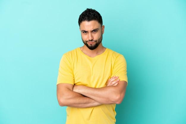 Молодой арабский мужчина изолирован на синем фоне, чувствуя себя расстроенным